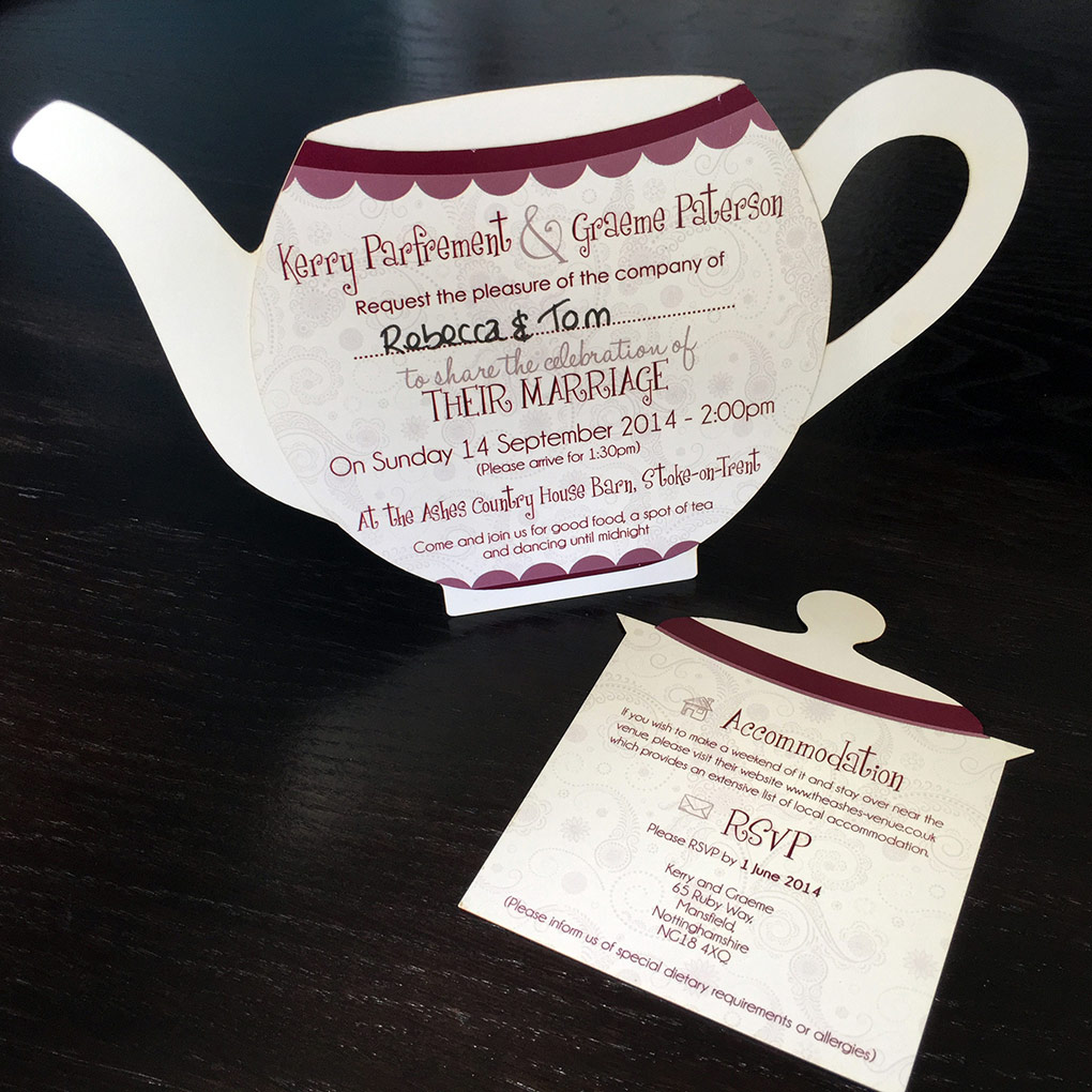 Teapot shaped wedding invitation stood up with removable insert placed in front of it